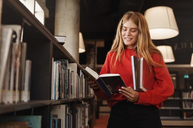 Rothaariges mädchen, student, der in der bibliothek nahe regalen steht, ein buch liest und lächelt.