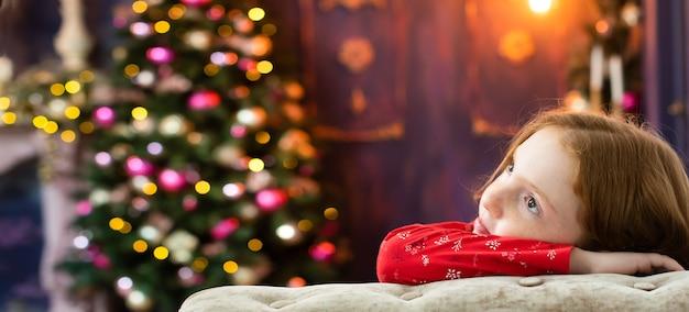 Rothaariges mädchen träumt von nahe dem weihnachtsbaum.