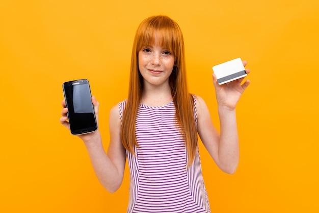 Rothaariges mädchen zeigt ein telefon und eine kreditkarte