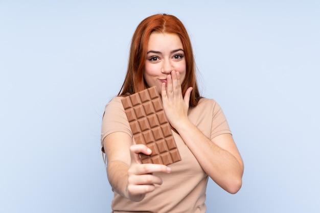 Rothaariges teenager-mädchen über blau, das eine schokoladentafel nimmt und überrascht