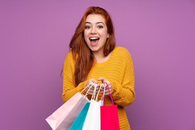 Rothaariges teenager-mädchen über isolierte lila wand, die einkaufstaschen hält und überrascht