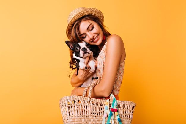 Rothaariges weißes mädchen, das im studio mit ihrem haustier aufwirft. gut aussehende junge dame im hut, die französische bulldogge auf hell hält.