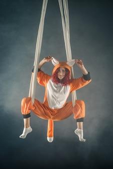 Rothaariges zirkusmädchen, das fanny trick auf luftseide im orangen fuchspyjama macht.