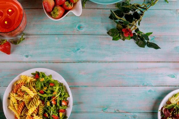 Rotini nudeln und grüner salat mit kerze und rose auf holztisch