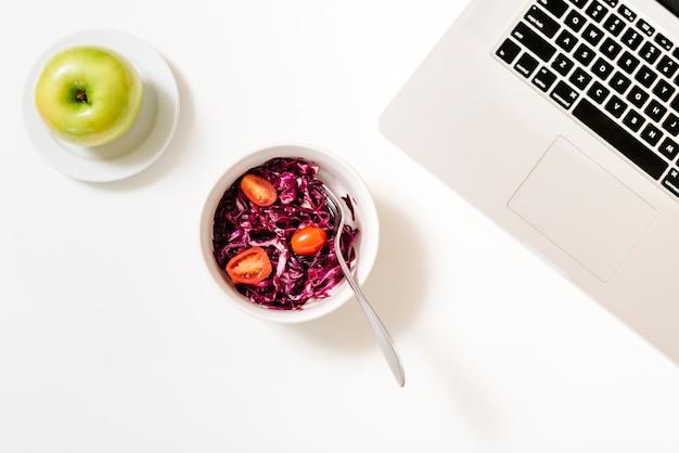 Rotkohl und tomaten in der schüssel nahe grünem apfel und laptop auf schreibtisch