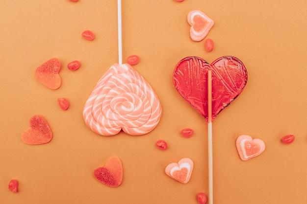 Rotrosa karamell- und marmeladenherzen auf einem orangefarbenen hintergrund. valentinstag .