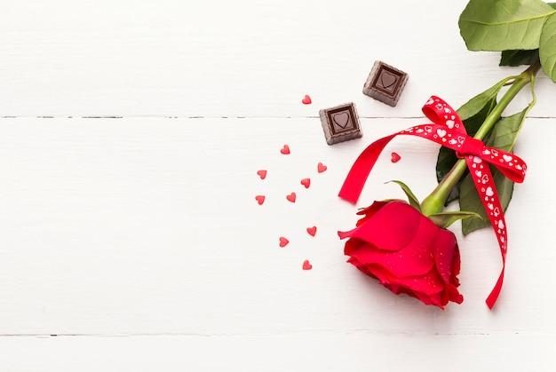 Rotrose, schokoladen auf einem weißen hölzernen hintergrund