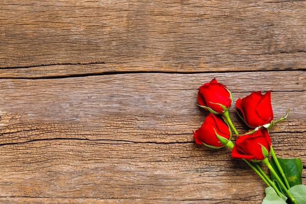 Rotrosenblume mit kopienraum auf hölzernem hintergrund. valentinstag-konzept