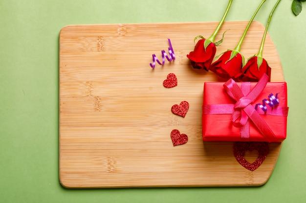 Rotrosenbündel und -geschenkbox auf hölzernem brett. valentinstag-konzept