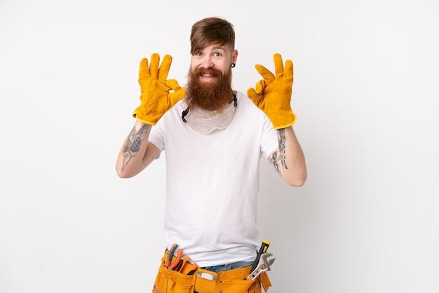 Rotschopf elektriker mann mit langem bart über isolierten weißen wand zeigt ein ok-zeichen mit den fingern
