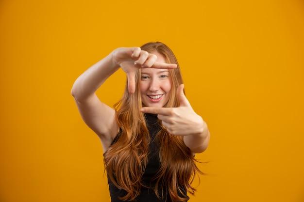 Rotschopf kaukasische frau über gelbe isolierte wand lächelnd, rahmen mit händen und fingern mit glücklichem gesicht machend. kreativitäts- und fotokonzept. filmemacher oder fotograf. lens vision idee.