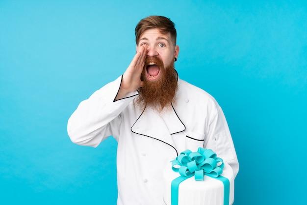 Rotschopf-konditor mit langem bart, der einen großen kuchen über isolierter blauer wand hält, die mit offenem mund schreit