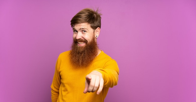 Rotschopf mann mit langem bart über lila wand zeigt finger auf sie mit einem selbstbewussten ausdruck