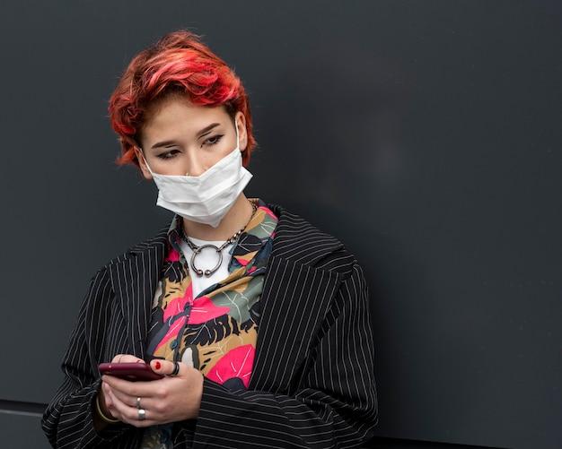 Rotschopf nicht binäre person, die eine medizinische maske trägt