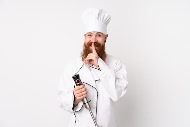 Rotschopfmann, der stabmixer über isolierte weiße wand verwendet, die schweigegeste tut