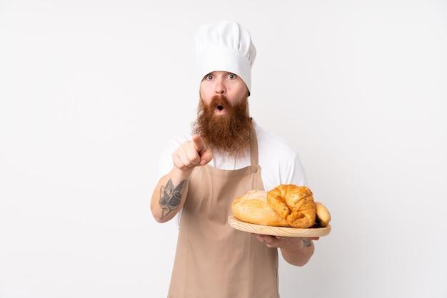 Rotschopfmann in kochuniform. männlicher bäcker hält einen tisch mit mehreren broten überrascht und zeigt nach vorne