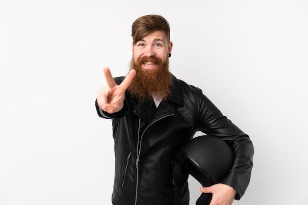 Rotschopfmann mit langem bart, der einen motorradhelm über isolierte weiße wand hält, die lächelt und siegeszeichen zeigt