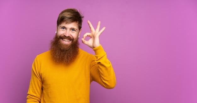 Rotschopfmann mit langem bart über isoliertem purpur, das ok zeichen mit den fingern zeigt