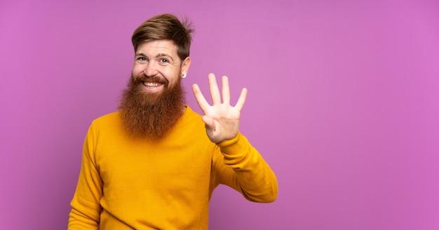 Rotschopfmann mit langem bart über isoliertem purpur glücklich und zählt vier mit den fingern