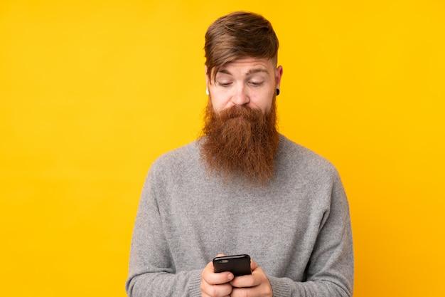 Rotschopfmann mit langem bart über isolierter gelber wand, die eine nachricht mit dem handy sendet