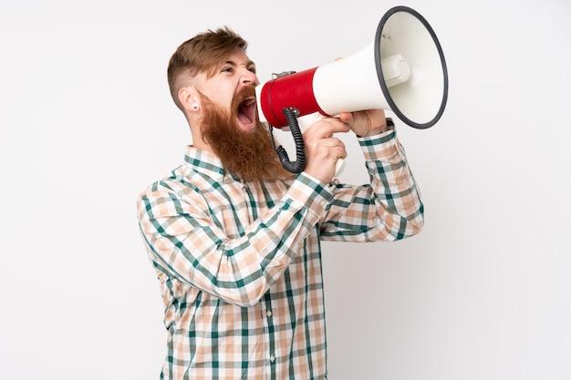 Rotschopfmann mit langem bart über isolierter weißer wand, die durch ein megaphon schreit
