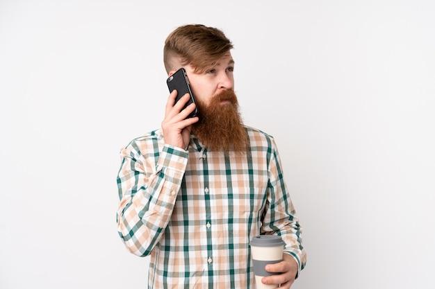 Rotschopfmann mit langem bart über isolierter weißer wand, die kaffee zum mitnehmen und ein handy hält