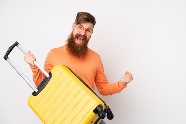 Rotschopfmann mit langem bart über isolierter weißer wand im urlaub, der einen reisekoffer wie eine gitarre hält