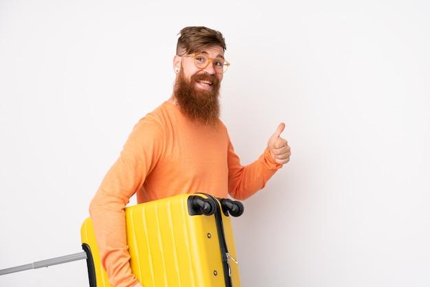 Rotschopfmann mit langem bart über isolierter weißer wand im urlaub mit reisekoffer und mit daumen nach oben
