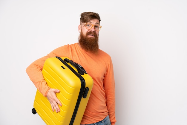 Rotschopfmann mit langem bart über isolierter weißer wand im urlaub mit reisekoffer
