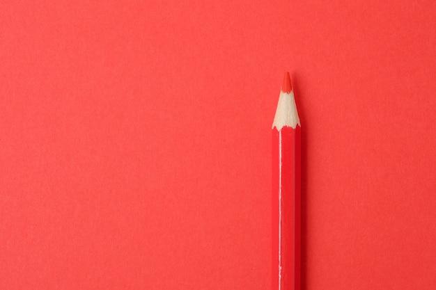 Rotstift auf rotem papierhintergrund. nahansicht.