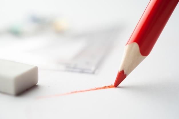 Rotstift schreibt auf papier.
