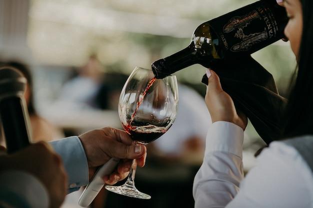 Rotwein aus der flasche in das weinglas gießen