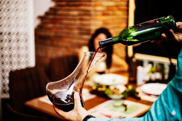Rotwein aus der flasche in ein glas geben.