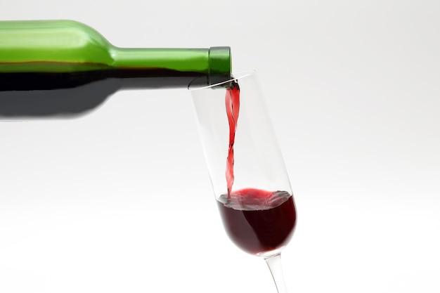 Rotwein aus der grünen flasche wird in ein glas gegossen