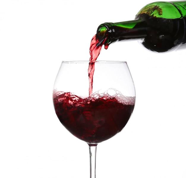 Rotwein, der auf weißen hintergrund gießt