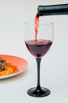 Rotwein, der in ein glas gießt
