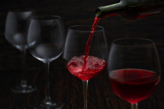 Rotwein, der in gläser von der flasche gießt