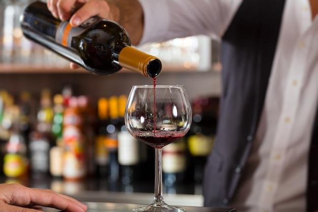 Rotwein, der in glas an der bar gießt