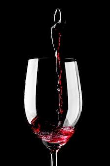 Rotwein, der in glas lokalisiert auf schwarzem hintergrund gießt