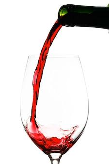 Rotwein, der in glas lokalisiert auf weißer wand gießt
