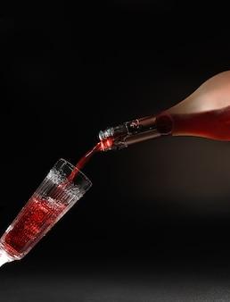 Rotwein, der in weinglas auf schwarz fließt