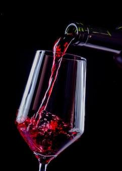 Rotwein, der in weinglas aus einer flasche gießt