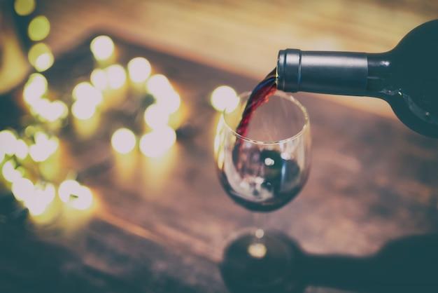 Rotwein, der in weinglas gießt.