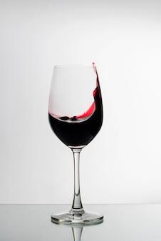 Rotwein, der oben die seite eines weinglases spritzt