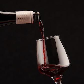 Rotwein gießt in weinglas auf schwarzem hintergrund
