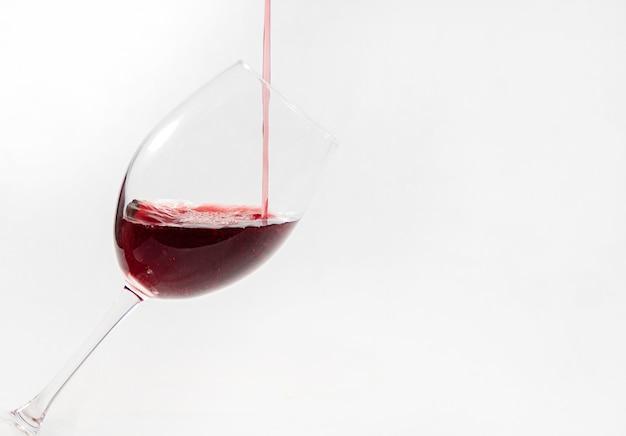 Rotwein goss in ein auf weiß isoliertes glas