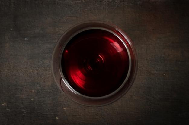 Rotwein im weinglas auf holz