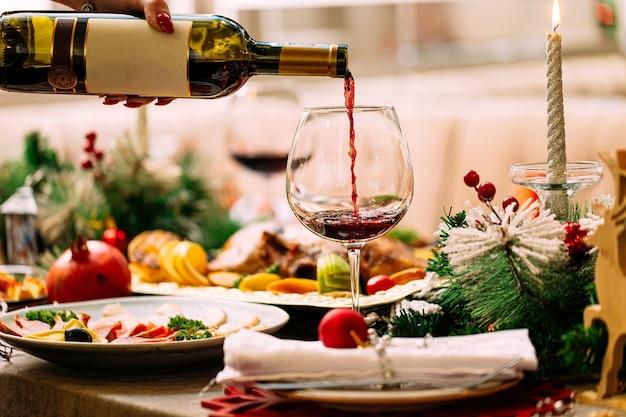 Rotwein in ein glas auf dem neujahrstisch gießen