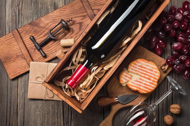 Rotwein in einem kasten mit einem glas-, korkenzieher- und frischkäse auf einer hölzernen alten tabelle. draufsicht mit platz für ihre grüße.