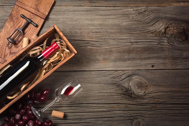 Rotwein in einem kasten mit einem glas und einem korkenzieher auf einem holztisch. draufsicht mit platz für ihre grüße